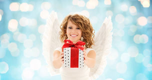 Happy woman with angel wings and christmas gift. People, holidays, christmas and birthday concept - happy young woman with angel wings holding gift box over stock images
