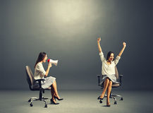 Happy woman and angry woman over dark Royalty Free Stock Image