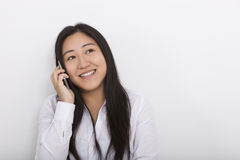 Happy woman answering cell phone against white background Royalty Free Stock Images