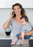Happy woman answering smartphone while carrying baby Royalty Free Stock Photography