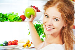 Happy woman with apple and open refrigerator with fruits, vegeta Stock Photos