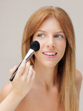 Happy woman applying blusher with brush Stock Image