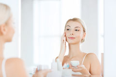 Happy woman applying cream to face at bathroom Stock Photos