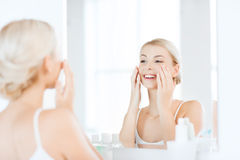 Happy woman applying cream to face at bathroom Stock Image