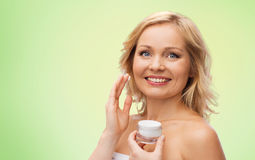 Happy woman applying cream to her face Stock Photo