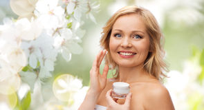Happy woman applying cream to her face Stock Image