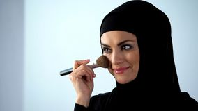 Happy woman applying face blush, face contouring, preparing for event, cosmetics royalty free stock image