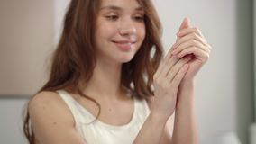Happy woman applying hand cream at morning. Female skincare concept. Portrait of smiling woman apply cream to hands at home. Close up of sensual girl applying stock video