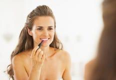 Happy woman applying lipstick in bathroom Stock Photo