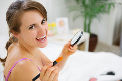 Happy woman applying make up in bedroom Stock Photo