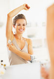 Happy woman applying roller deodorant on underarm in bathroom Royalty Free Stock Photography