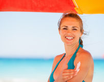 Happy woman applying sun block creme on arm Royalty Free Stock Photo