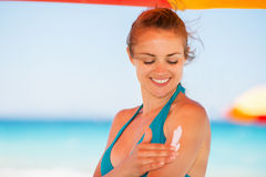 Happy woman applying sun screen creme Stock Photo