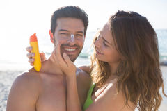 Happy woman applying sunscream on smiling man face at beach Royalty Free Stock Photo
