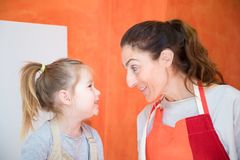 Happy woman with apron looking at her smiling daughter Royalty Free Stock Photography