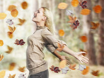 Happy Woman With Arms Outstretched Amid Fall Leaves. Side view of a happy young blond woman standing with arms outstretched amid autumn leaves Stock Photo
