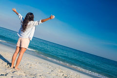 Happy woman with arms outstretched at the beach Royalty Free Stock Photography