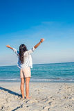 Happy woman with arms outstretched at the beach Stock Photos