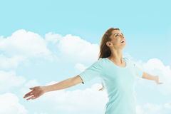 Happy Woman With Arms Outstretched Standing Against Cloudy Sky Stock Photo
