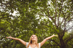 Happy woman with arms raised in park Stock Photo
