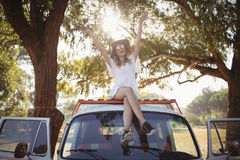 Happy woman with arms raised on van Stock Image