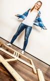 Happy woman assembling wood furniture. DIY. Royalty Free Stock Image