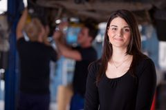 Happy Woman Auto Repair Customer. A happy female auto repair customer looking at the camera with a smile stock image