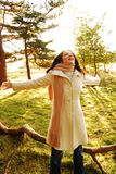 Happy woman in Autumn. A happy woman throwing her arms up in an autumn scene royalty free stock image