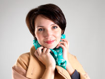 Happy woman in autumn coat with green scarf. Portrait of happy woman in beige autumn coat with green scarf at studio on the grey background stock images