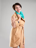 Happy woman in autumn coat with green scarf. Portrait of happy woman in beige autumn coat with green scarf at studio on the grey background royalty free stock photography
