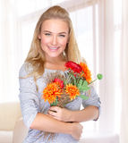 Happy woman with autumn flowers. Portrait of beautiful happy woman with autumn flowers at home, receive gift on Thanksgiving day, happiness concept royalty free stock images