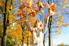 Happy woman  with autumn leav. Portrait of a happy woman playing with autumn leaves Stock Photos