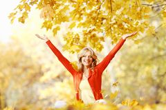 Happy woman in autumn park. Drop up leaves Royalty Free Stock Image