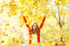 Happy woman in autumn park. Drop up leaves Stock Photos