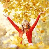 Happy woman in autumn park. Drop up leaves Stock Images