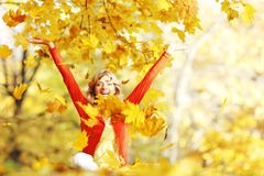 Happy woman in autumn park. Drop up leaves Stock Image