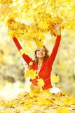 Happy woman in autumn park. Drop up leaves Royalty Free Stock Photography