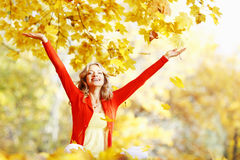 Happy woman in autumn park. Drop up leaves Royalty Free Stock Photo