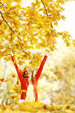 Happy woman in autumn park. Drop up leaves Royalty Free Stock Images