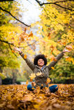 Happy woman in autumn park drop up leaves. Girl playfully throwing up fallen autumn leaves over her head Stock Images