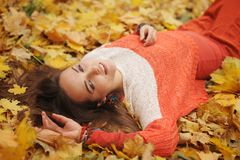 Happy woman autumn portrait, lying in autumn leaves. Dressed in fashion sweater royalty free stock images