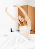 Happy woman awaking on white sheet Royalty Free Stock Photos