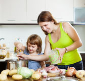 Happy woman with baby cooking with grains Stock Images