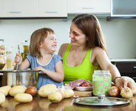 Happy woman with baby cooking   at  kitchen Stock Images