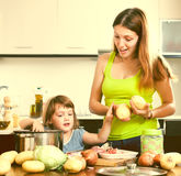 Happy woman with baby cooking with potatoes Stock Photography