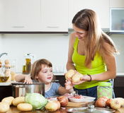 Happy woman with baby cooking Stock Photos