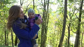 Happy woman with baby girl in arms walk in autumnal park. 4K stock video