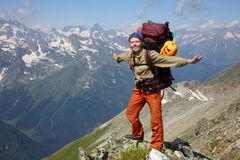 Happy woman with backpack. Standing on a mountain jad Stock Photos