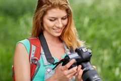 Happy woman with backpack and camera outdoors Stock Images