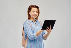 Happy woman with backpack and tablet computer. Travel, tourism and technology concept - happy woman with backpack and tablet computer over grey background royalty free stock images